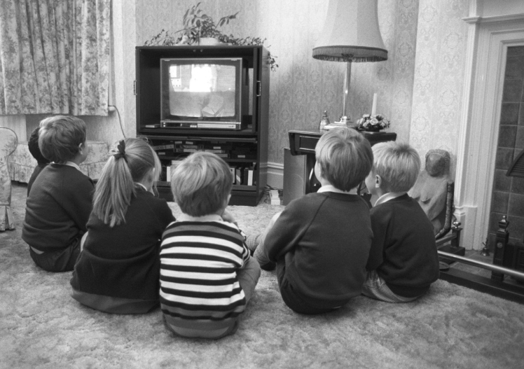 A group of young British children watching television in October 1988. (Photo by Express/Getty Images)